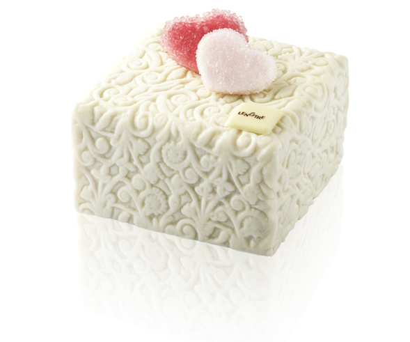 Le cube des amoureux. Ceux qui se seront laissés tenter par un week-end en amoureux pourront glisser dans leur sac un appétissant gâteau de voyage en forme de cube à transporter et à partager. Ce surprenant biscuit moelleux, sans beurre et sans gluten, est fourré d'une crème au goût de calisson et d'une délicieuse compotée d'oranges, enveloppé d'une pâte d'amandes blanche, ornée d'exquises friandises cœurs en sucre candy. Pour 2 personnes (16 €). © T.Dhellemmes